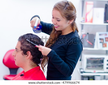 Spontaneus and smiling hairstylist is getting wet her next client, comb and spray on her hands