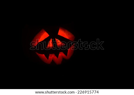 Spooky carved halloween pumpkin on black background lit by a candle - stock photo