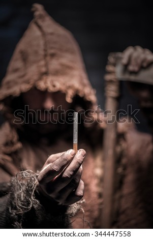Spooky epitome of death is standing and holding a cigarette. The man is waiting for you to smoke and dye with anticipation. He is carrying a scythe - stock photo
