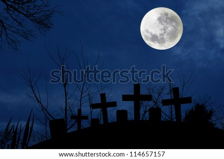 Spooky graveyard with full moonlight in the dark night of halloween
