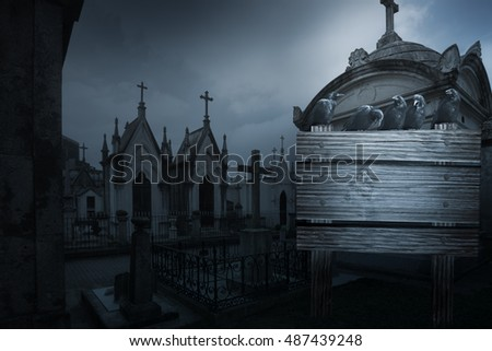Spooky halloween background with crows, tombs in the form of chapel from an old european cemetery street and wooden placard in the foreground with space to write
