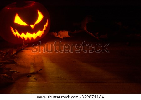 Spooky halloween background with face of jack o lantern in the corner with red shadows on the wooden surface with autumn dried leaves