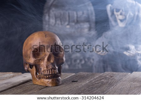 Spooky halloween human skull with grim reaper and tombstone in background - stock photo