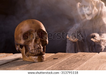 Spooky halloween human skull with grim reaper in background - stock photo