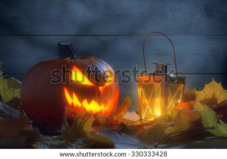 Spooky halloween jack o lantern face among autumn leaves during night with lighting lantern by wooden wall - stock photo