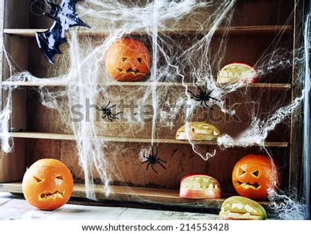 Spooky Halloween pantry with pumpkin lanterns and apples shaped as open mouths with teeth on wooden shelves draped in spider webs crawling with large black spiders - stock photo
