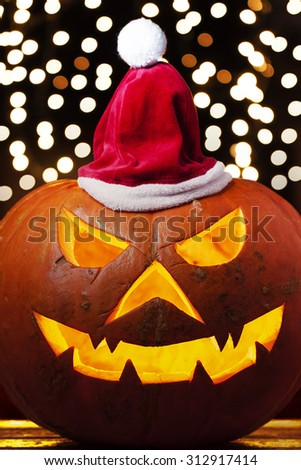Spooky halloween pumpkin Jack O Lantern shiny inside wearing christmas hat on out of focus lights background - stock photo