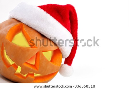 Spooky halloween pumpkin Jack O Lantern shiny inside wearing christmas hat on white background - stock photo