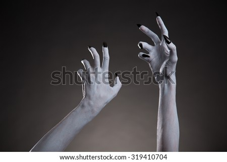 Spooky Halloween white hands with black nails stretching up, body art - stock photo