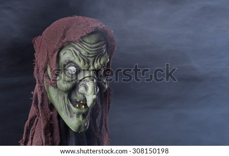 Spooky halloween witch prop on a smoky background - stock photo