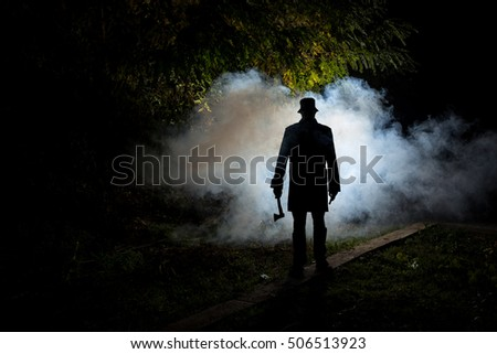 spooky horror man with an axe in the foggy night