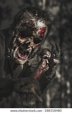 Spooky horror photograph of an evil male zombie with rotten face shouting out in bloody terror at dark haunted forest. The bone collector - stock photo