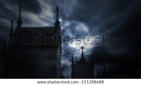 Spooky image with old European cemetery in a dark night with cloudy threatening sky; Good for halloween. - stock photo