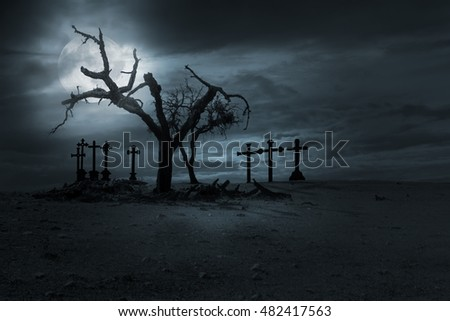 Spooky naked trees and christian cemetery crosses against a cloudy sky in a full moon night. Good as halloween background.