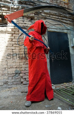 Spooky person in red hood threatening with his scythe - stock photo
