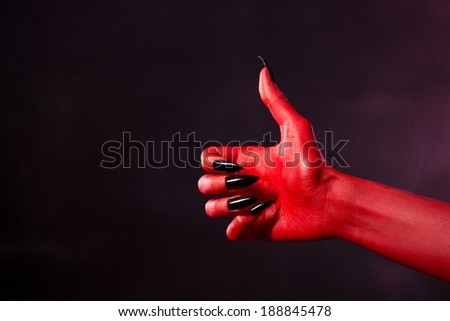 Spooky red devil hand with black nails showing thumbs up, studio shot on smoky background  - stock photo