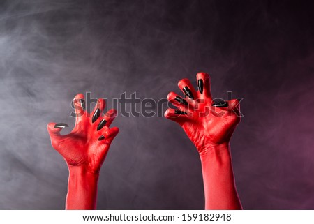 Spooky red devil hands with black glossy nails, Halloween theme, studio shot over smoky background  - stock photo