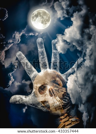 Spooky skull combined with dirty palm on nightly sky and clouds with bright full moon for halloween background. Hand up to sky. The moon taken with my own camera, no NASA images used. - stock photo