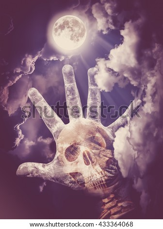 Spooky skull combined with dirty palm on nightly sky and clouds with bright full moon for halloween background. Hand up to sky. The moon taken with my own camera, no NASA images used. Vintage tone. - stock photo