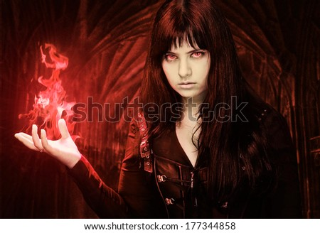 Spooky woman with fire in her hand - stock photo