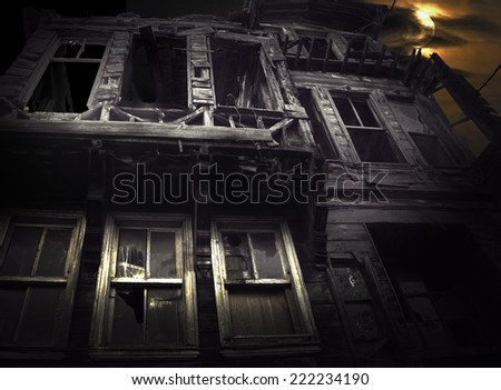 Spooky wooden building on moody night sky with full moon - stock photo