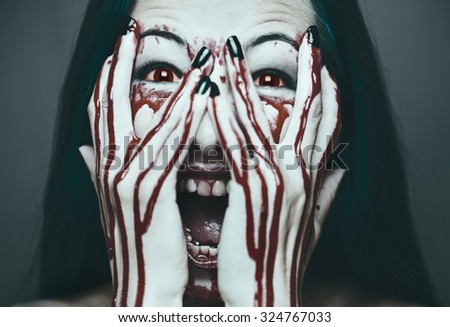 Spooky young woman screaming, her face and hands in blood. Halloween and horror theme. Monochrome image