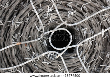 spool of barbed wire used for building fences and construction - stock photo