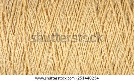 Spool of beige thread macro background  - stock photo
