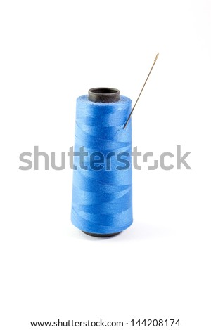 Spool of blue thread and needle - stock photo