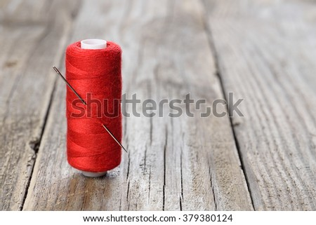 Spool of red thread with needle on wooden table