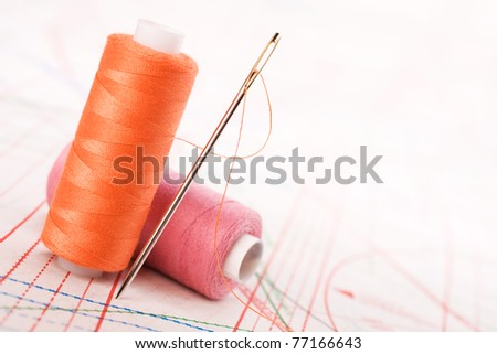 Spool of thread and needle. Sew accessories on blurred background.