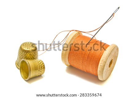 spool of thread, and thimbles on white - stock photo