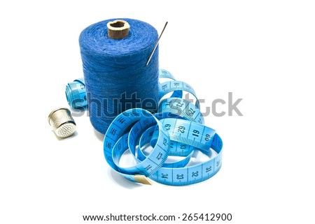 spool of thread with needle, meter and thimble on white background - stock photo