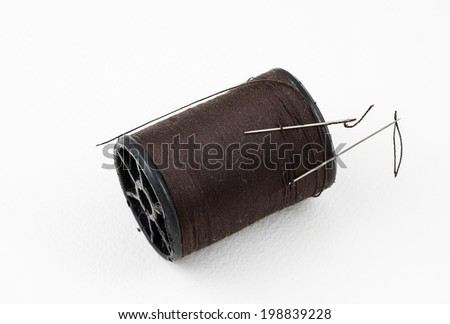 spool of thread with needle on white background - stock photo