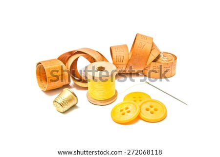 spool of yellow thread, thimble and buttons on white background - stock photo