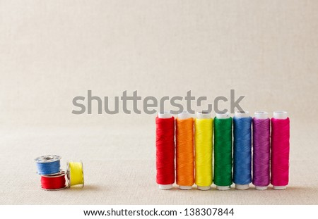 Spools and bobbins of thread, brightly coloured, arranged in rainbow colour formation - stock photo