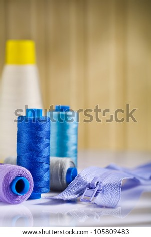 spools and zip on white table