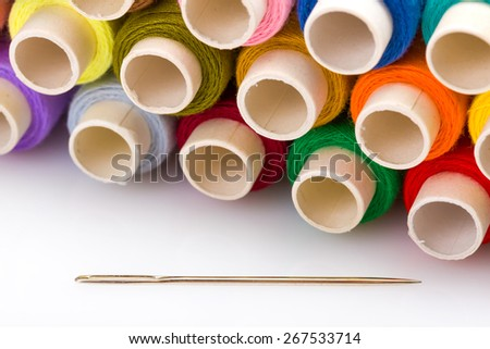 Spools of colorful threads with sewing needle - stock photo