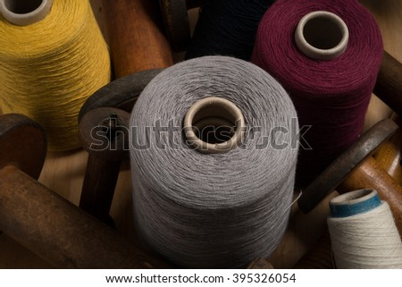 Spools of grey, red, yellow, and white thread surrounded by empty old wooden spools. - stock photo