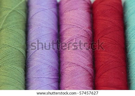 spools of many colors of thread and textiles - stock photo