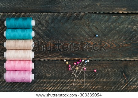 Spools of thread and pins on old wooden background. Sewing accessories. Top view - stock photo