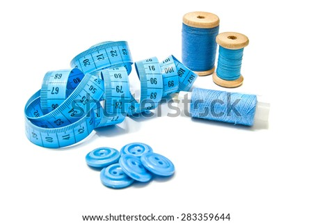 spools of thread, buttons and meter on white  - stock photo