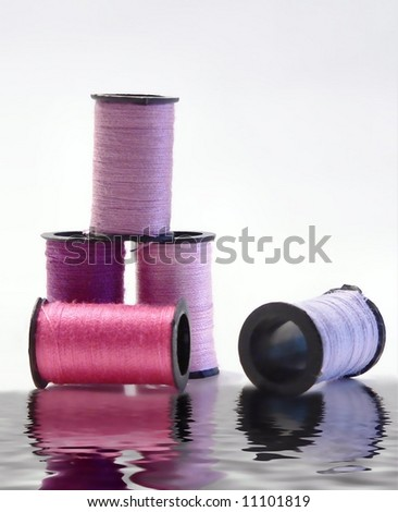 spools of thread in cool shades of pink and purple with reflection