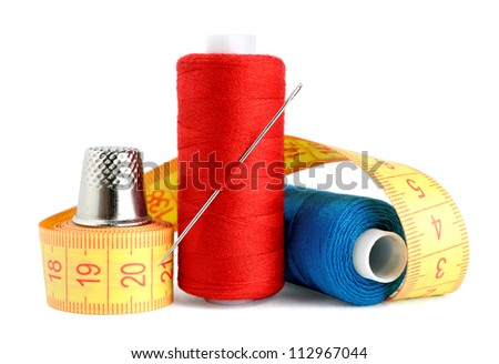 Spools of thread, needle, measuring tape and thimble isolated on white background - stock photo