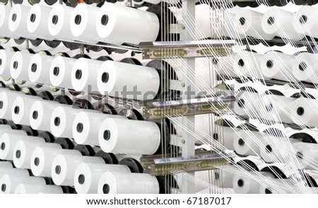 Spools of thread on a loom - stock photo