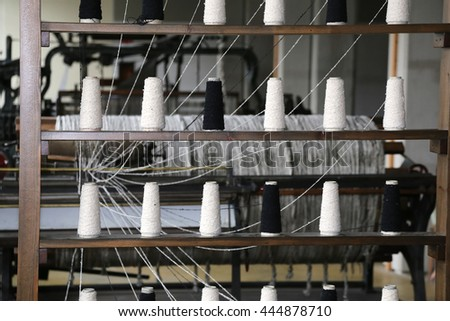 spools of thread to spin in the old industrial weaving loom fabrics in the textile industry of the last century - stock photo
