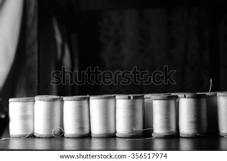 spools of white thread over a black background