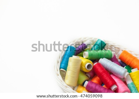 Spools with color threads for sewing lie in a white basket.