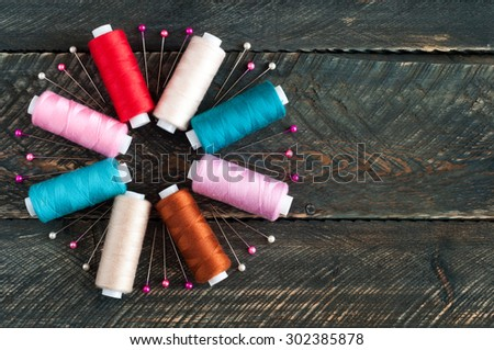 Spools with different colors of thread and pins on old wooden background. Sewing accessories. Top view - stock photo