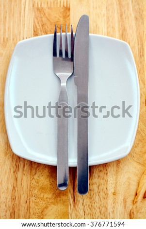 Spoon and fork in a dish on wood table. - stock photo